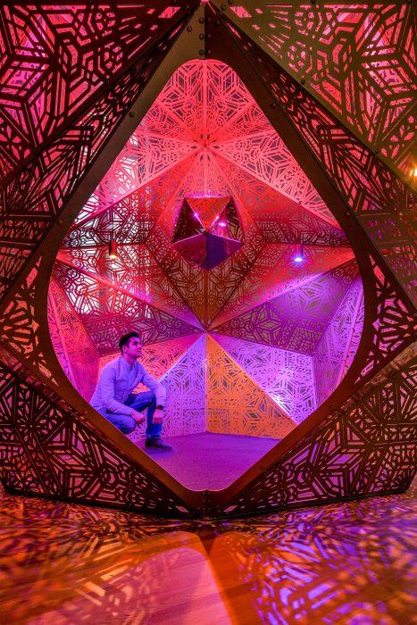 Man sitting inside intricate sphere