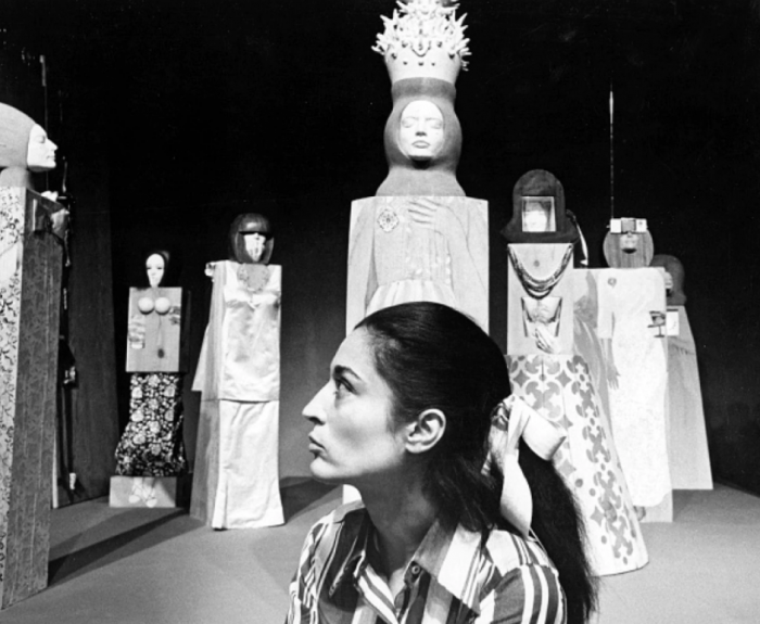 B&W photo of artist with sculptures