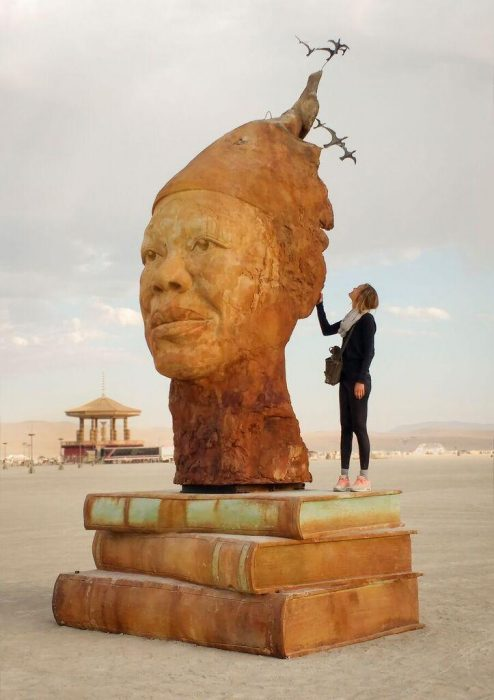 Sculpture of woman's head atop books