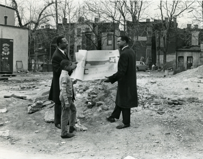 Two men and child look at blueprints in vacant lot