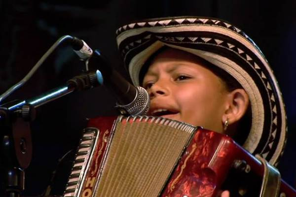 close up of child playing accordion and singing