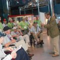 Elderly men in wheelchairs listen to tour guide