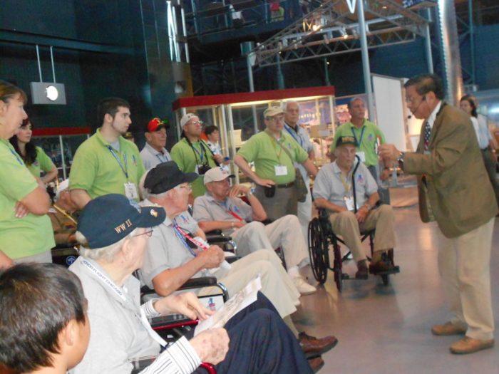 Elderly men in wheelchairs listen to tour guide