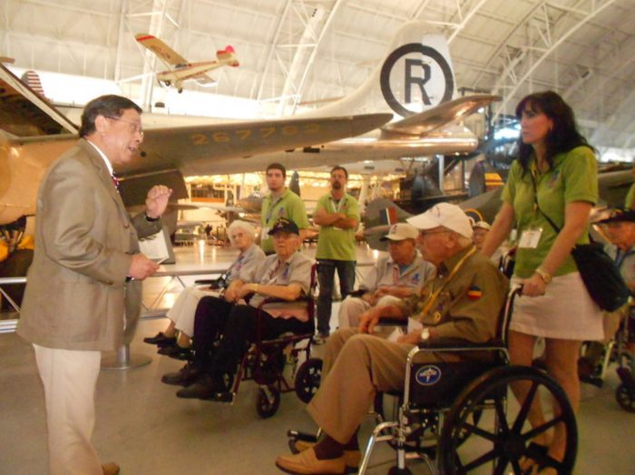 Veterans in wheelchairs listen to docent