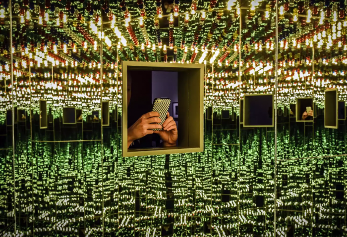 Cell phone reflected in mirrored exhibition