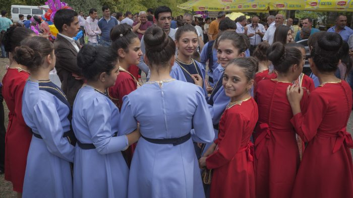 Young costumed dancer prepare to perform; one smiles for camera