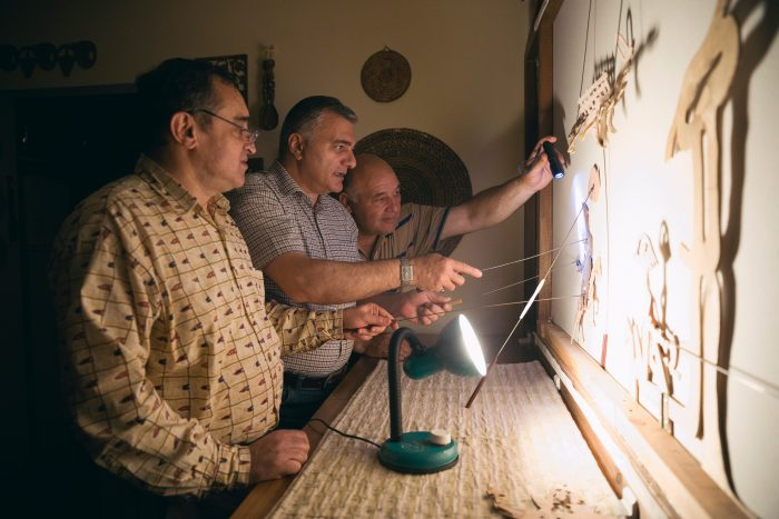 Men working with wooden puppets