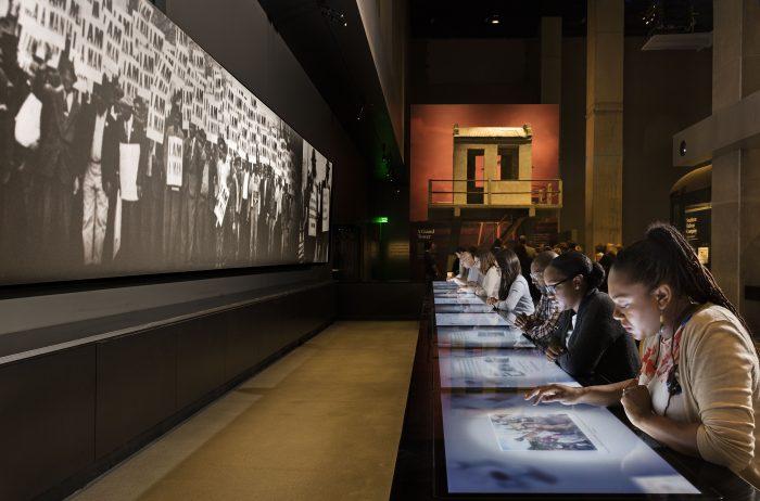 Visitors sit at long interactive counter