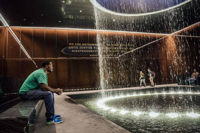Man sits on bench in front of fountain