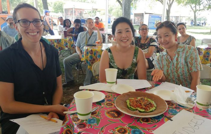 Three women smiling over winning plate of food