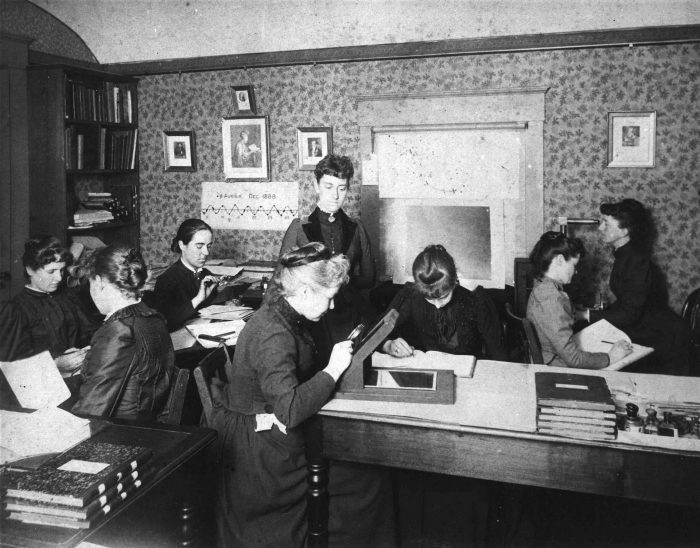 Women making calculations in crowded workroom