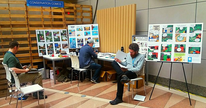 People examining conservation comics on display board