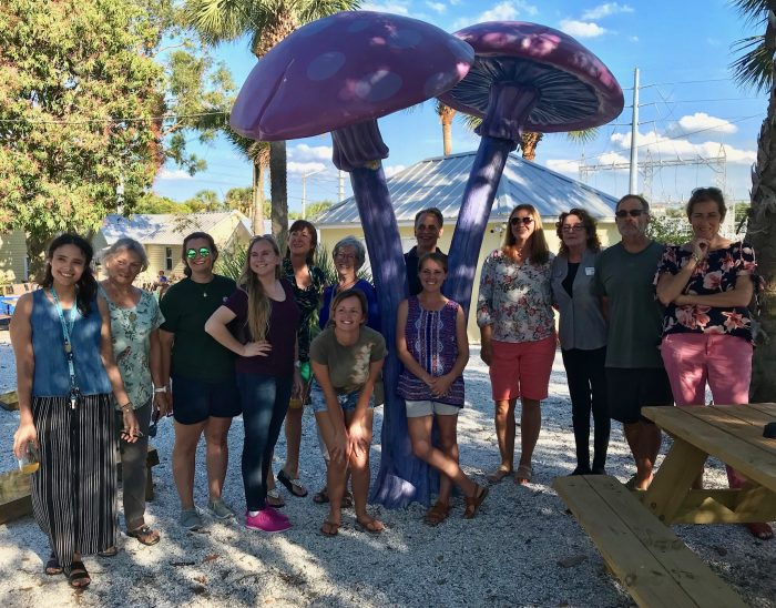 Volunteers gather under mushroom sculpture