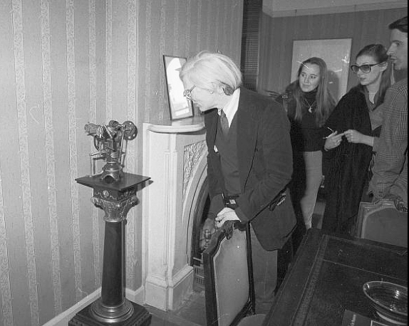 Warhol looking at elaborate model on pedestal. Unidentified women in background