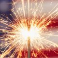 Sparkler with American flag in backgroun