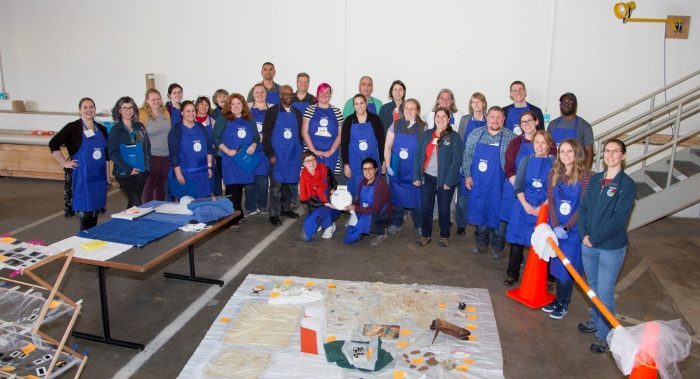 Gorup photo of participants in blue aprons