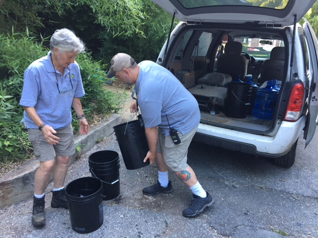 Man and woman loading buckets into back of SUV