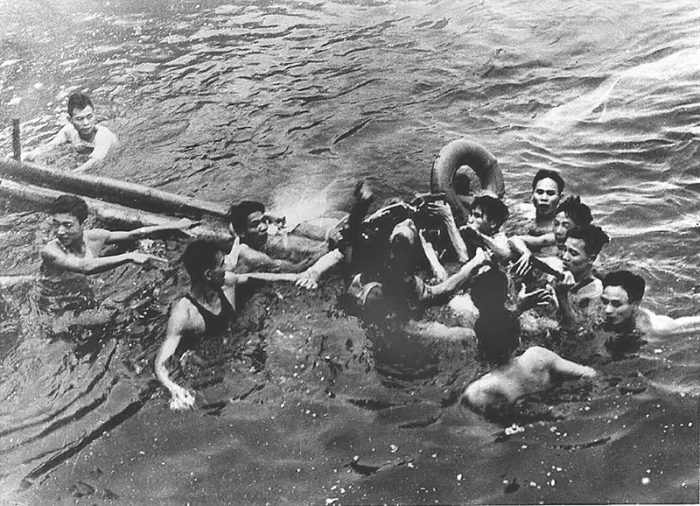 McCain in the water, surrounded by Vietnamese men