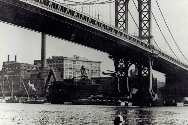 Black and white photo of plane flying under bridge