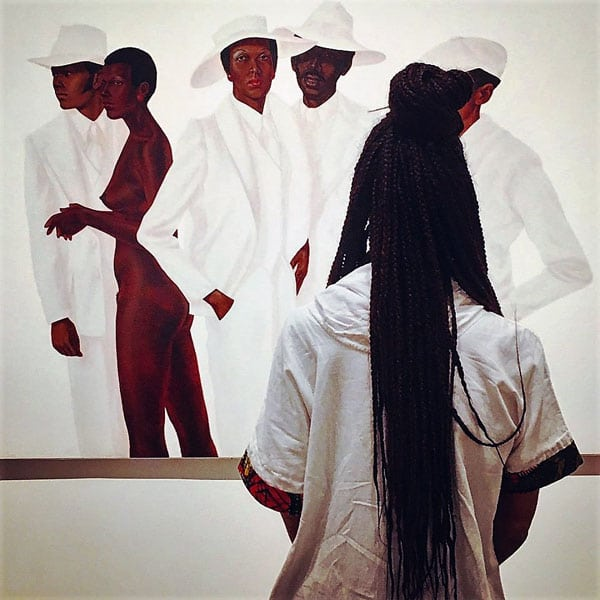 Black woman in gallery looks at painting of African American people