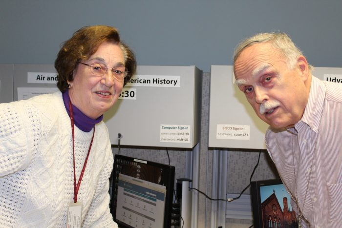 Two volunteers pose in front of their desks
