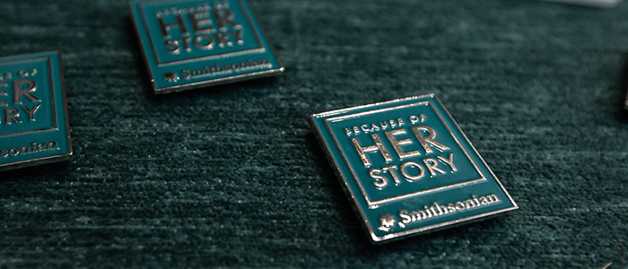 "Close up of ""Because of Her Story"" pins"