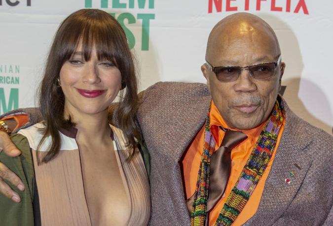 Rashida and Quincy Jones pose in front of scrim