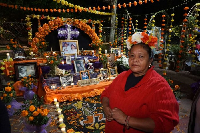 Woman stands before elaborate Day off the Dead altar