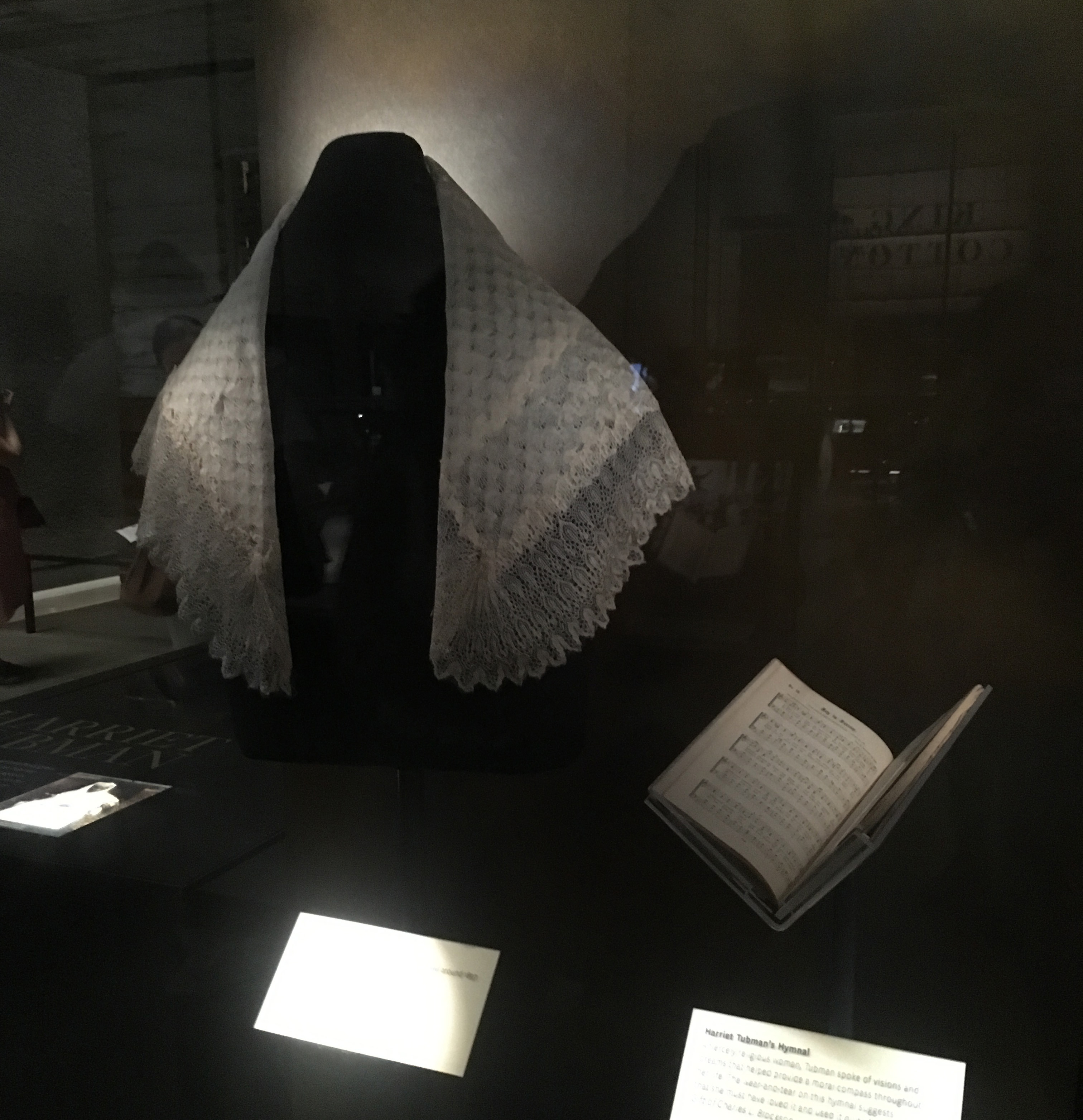 Shawl and hymnal in display case