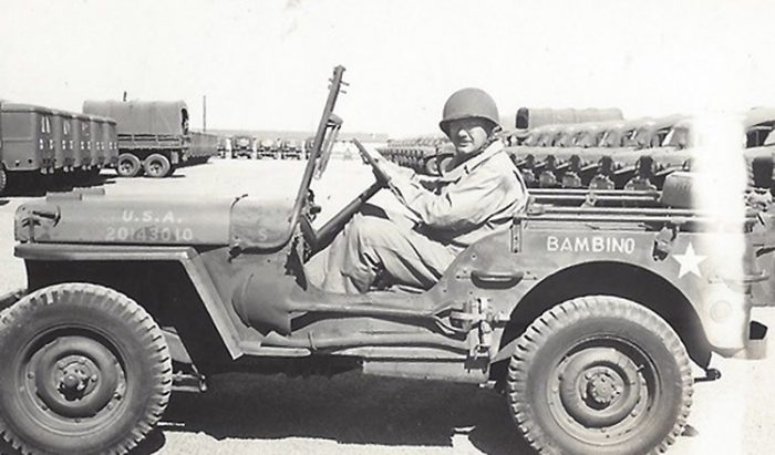 Soldier poses in jeep