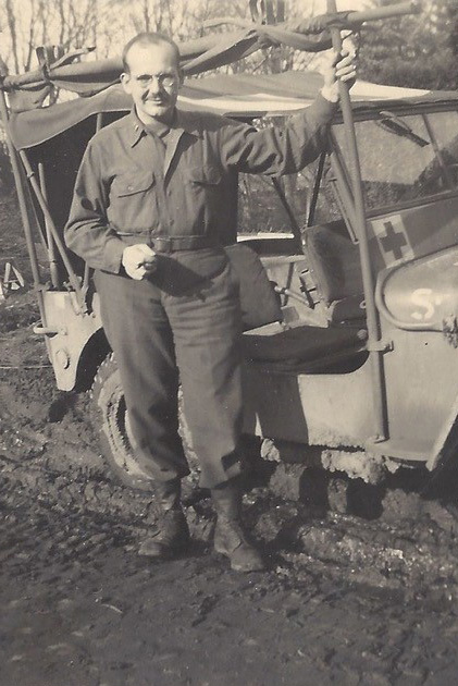 Soldier poses next to jeep