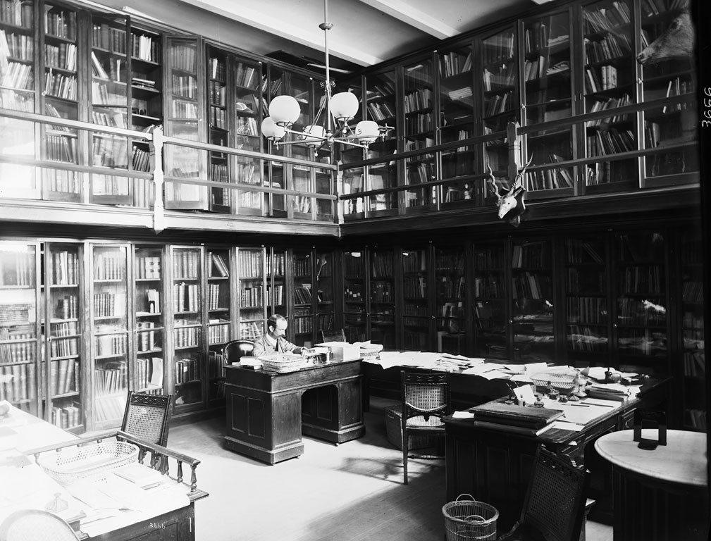 Black and white photo of librarian at desk among two-story bookshelves