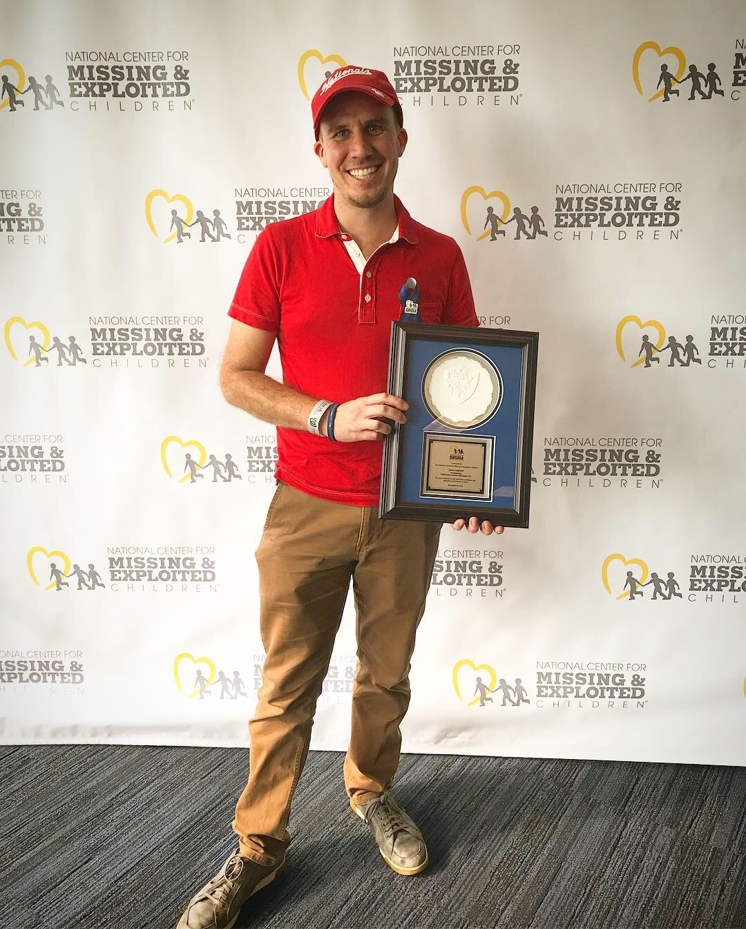 Gagliardi in red shirt and cap in holding award in front of step-and-repeat screen