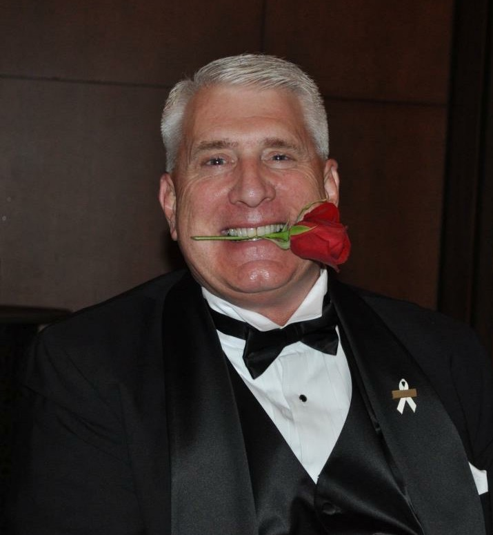 Peterson in tuxedo with rose in his teeth