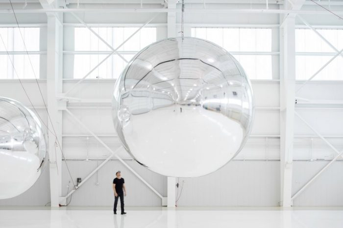 Artist in front of spherical installation