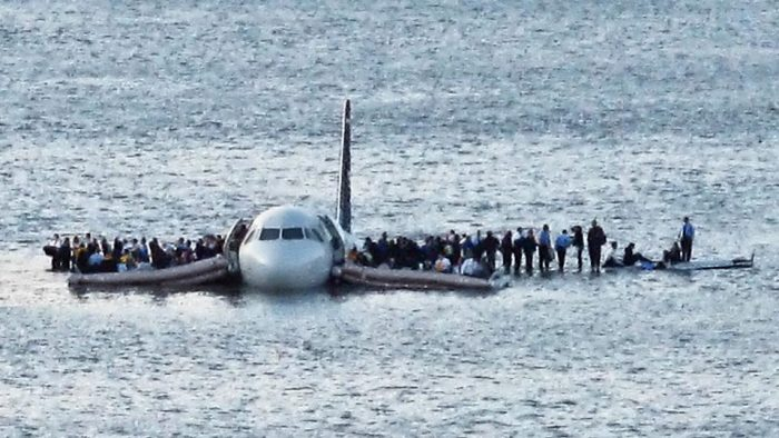 Passengers standing on wings of downed plane