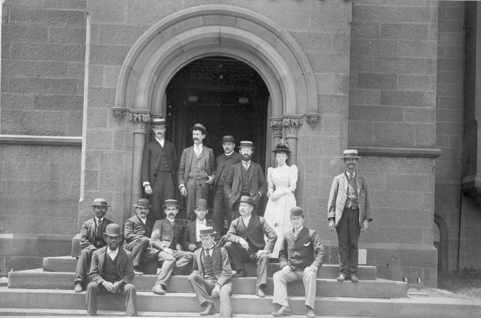 Group, including one woman, poses on Smithsonian Castle steps.)