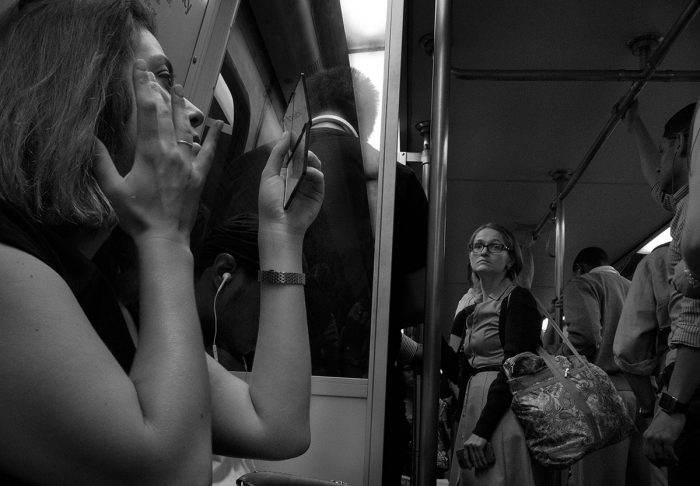 Woman doing her makeup on Metro train