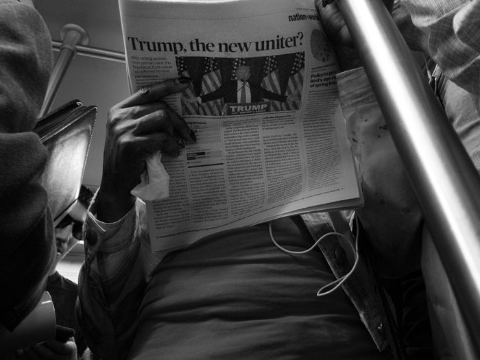 Commuter reading newspaper with Trump headline