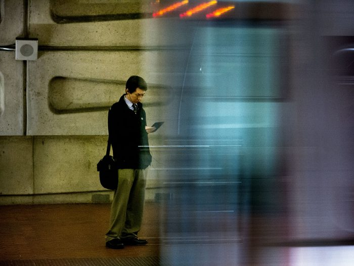 Commuter looking at phone as train goes by