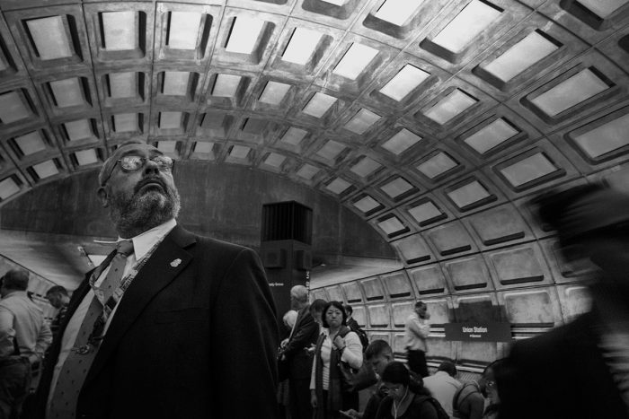 Commuters in Metro station, man in glasses looking upward