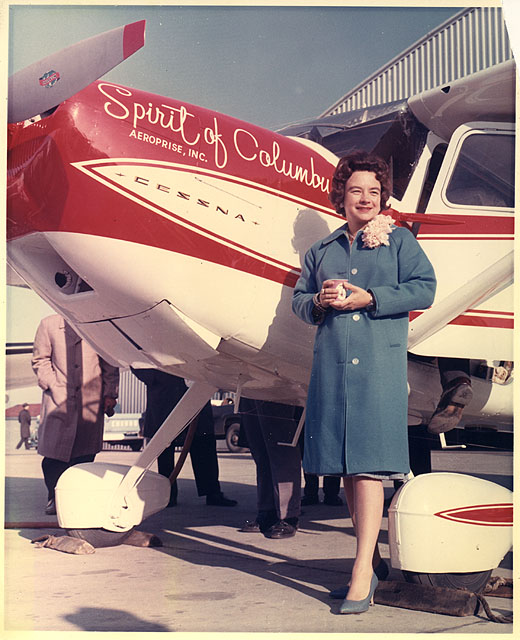 Mock in coat dress and corsage poses beside her plane