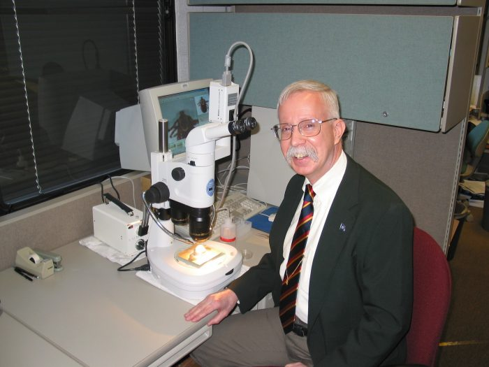 Robbins at desk with microscope
