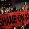 "Protesters holding red banner ""Shame on Sackler"""