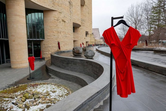 Red dresses on hangers on plaza of NMAI