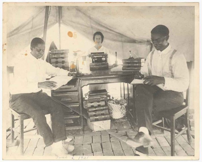 B&W photo of two men and woman with law office set up in tent