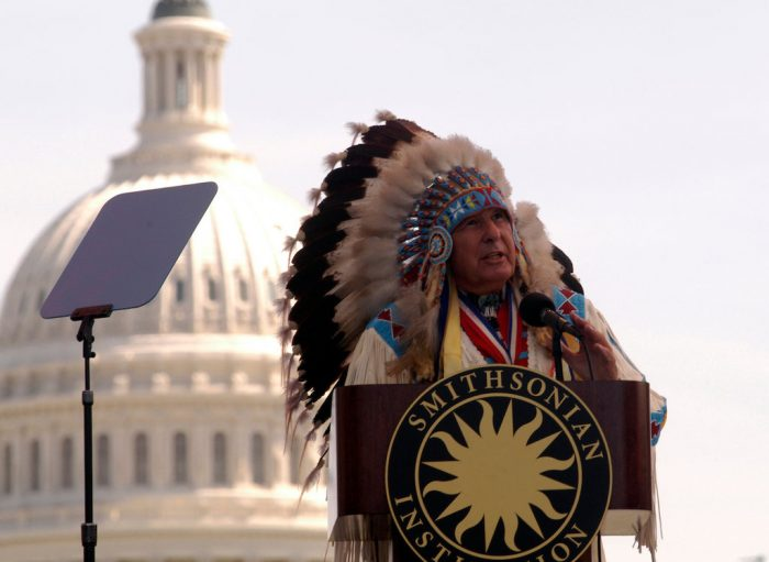 Native American in full regalia speaks in front of the Capitol