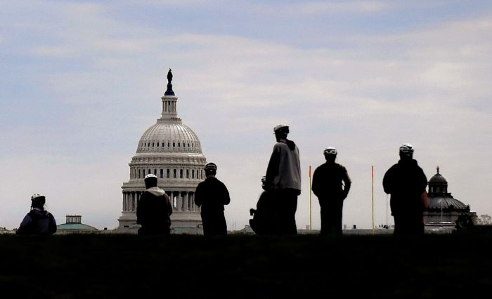 Tourists silhouetted against Capitol building