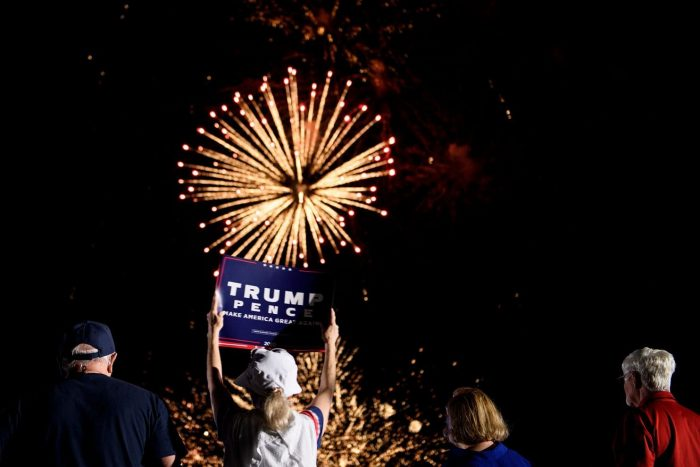 Supporter holding Trump sign with fireworks in background