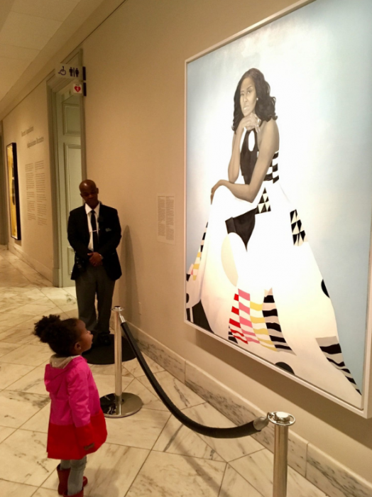 Child stands in front of portrait of Michelle Obama